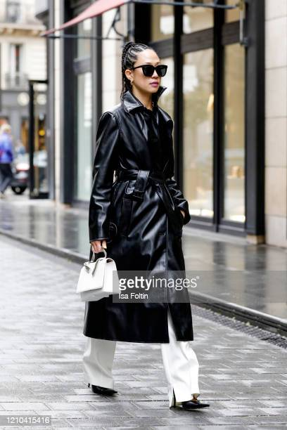 US influencer Kim Bui Kollar wearing a black leather coat by Commission NYC white pants by 31 philipp Lim jewelry by Light Miller a bag by Letrange...