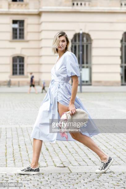 Influencer Kimyana Hachmann wearing a ra light blue dress by Gestuz, a beige bag by unknownstore and blue patterned sneakers by Dior during a street...