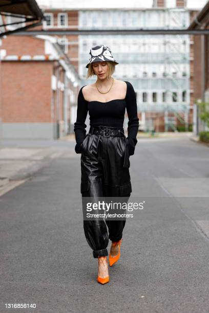 """Influencer Lisa Hahnbueck wearing a black ripped knit """"u2018The Maddy""""u2019 top with sweetheart neckline by Khaite, a black and white bucket hat by..."""