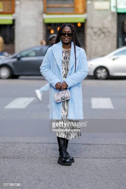 Influencer Lois Opoku wearing a blue coat by Kaos a safari dress by Kaos boots by Jeffrey Campbell a black and white safari bag by Weat and...
