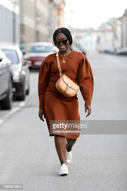Influencer Lois Opoku wearing a brown dress by Baum und Pferdegarten white sneakers by Converse a light brown bag by Dior and sunglasses by Saint...