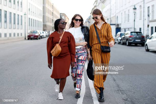 Influencer Lois Opoku, wearing a brown dress by Baum und Pferdegarten, white sneakers by Converse, a light brown bag by Dior and sunglasses by Saint...