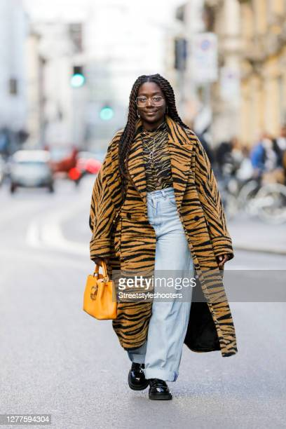 Influencer Lois Opoku, wearing a tiger colored coat with tiger pattern by Lala Berlin, a tiger colored shirt with tiger pattern by Lala Berlin, a...