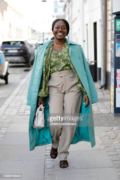 Influencer Lois Opoku wearing a turquois coat by Remain, a green patterned blous by Copenhagen Muse, beige pants by Inwear, black sandals by H&M, a...