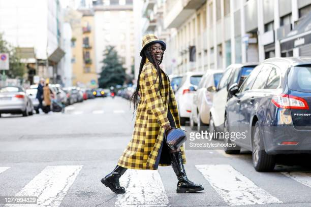 Influencer Lois Opoku, wearing a yellow checked coat and hat by Baum und Pferdegarten, a black dress by Zara, black boots by Jeffrey Campbell and a...
