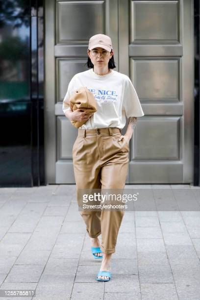 Influencer Maria Barteczko wearing a beige base cap by Asos a offwhite printed oversized Tshirt by Sporty Rich light brown leather pants by Zara...
