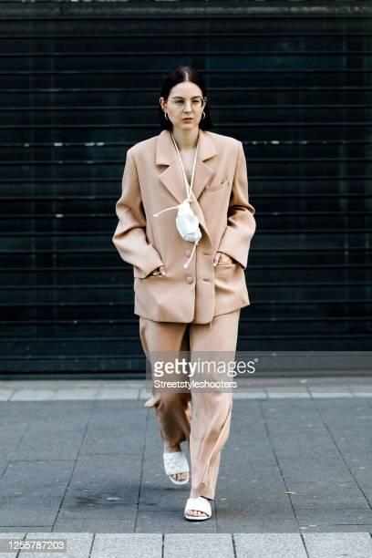 Influencer Maria Barteczko, wearing a beige oversized blazer by Salisa, beige wide leg slit pants by Salisa, a white leather pouch bag by Mango,...