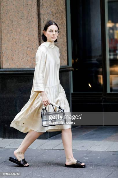 Influencer Maria Barteczko, wearing a beige silk midi ballon dress by Arket, black logo rubber slides by Chanel, a transparent pvc pearl bag by...