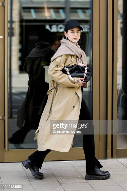 Influencer Maria Barteczko, wearing a black basecap by Asos, a beige trenchcoat by Zara, a white shirt by 032c, black slit leggings by Zara, a brown...