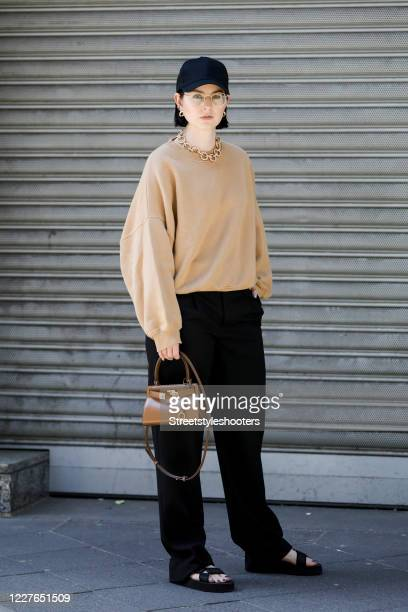 Influencer Maria Barteczko wearing a black basecap by Asos a brown oversized sweater by American Vintage black wide leg trousers by The Row a brown...