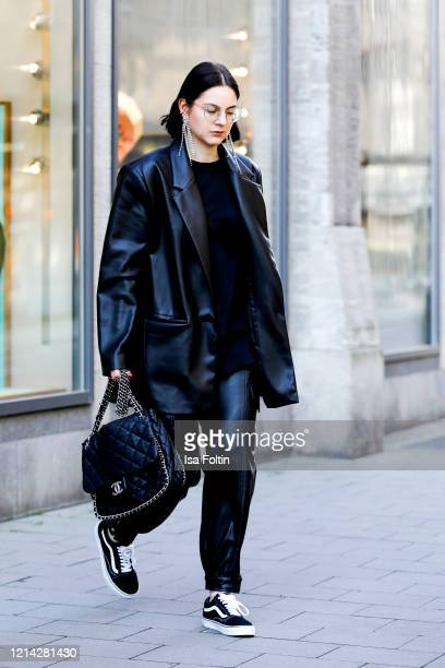 Influencer Maria Barteczko wearing a black leather blazer and black leather cargo pants by Zara a black oversized shirt by Arket black shoes by Vans...