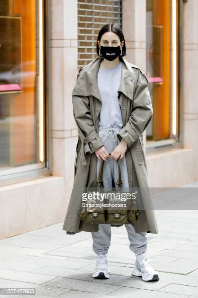 Influencer Maria Barteczko, wearing a black logo face mask by 2nd Couture, a green trenchcoat by The Frankie Shop, a grey basic shirt by H&M, white...