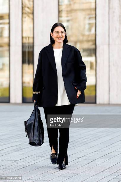 Influencer Maria Barteczko, wearing a black oversized blazer by The Frankie Shop, a white oversized shirt by Arket, black front slit leggings by...