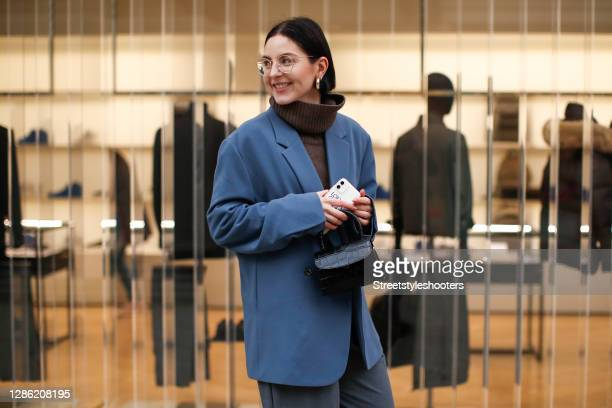 Influencer Maria Barteczko, wearing a blue oversized blazer by Seventh, a brown oversized cashmere turtleneck pullover by Arket, grey wide leg pants...