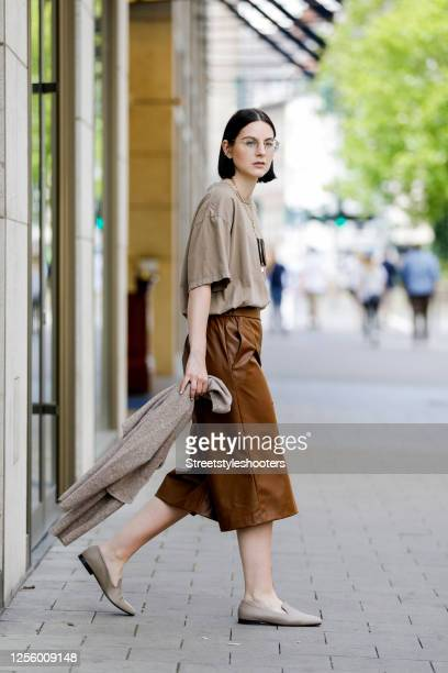 Influencer Maria Barteczko, wearing a brown oversized shirt by Hope, brown leather bermuda pants by Zara, taupe square toe leather loafer by Arket, a...