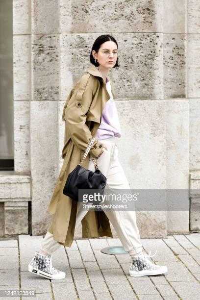 Influencer Maria Barteczko wearing a brown trenchcoat by Zara a light purple logo sweater by Nonouc studios beige jogging track pants by Bershka...