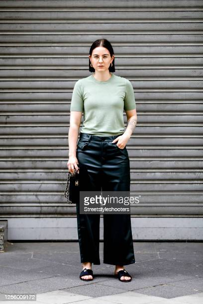 Influencer Maria Barteczko, wearing a green knit top by Zara, green wide leg leather pants by Zara, black satin mules by March & Muse, a black cotton...