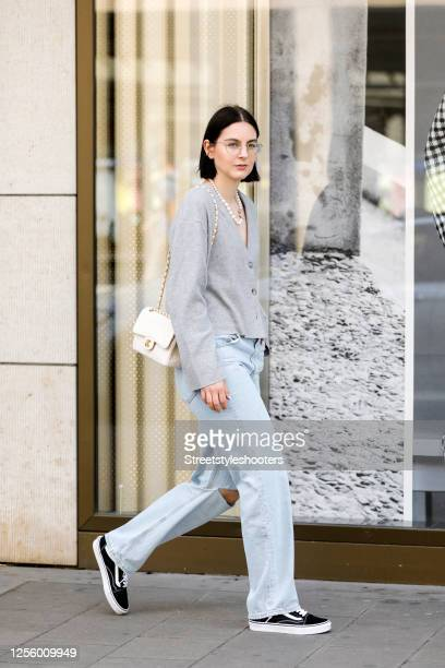 Influencer Maria Barteczko, wearing a grey cropped wool cardigan by Zara, a light denim destroyed boyfriend jeans by Zara, black cotton sneakers by...