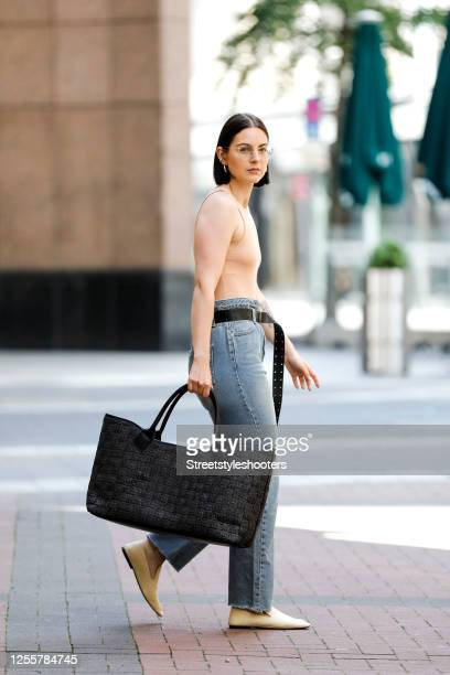 Influencer Maria Barteczko, wearing a nude sleeveless body by Zara, a denim high waist belted jeans by The Frankie Shop, a black straw shopper bag by...