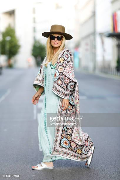Influencer Maria Gieseke wearing a light turquoise dress by Peace and Love by Calao, a multicolor hippie cape by Free People, a dark beige hat by...