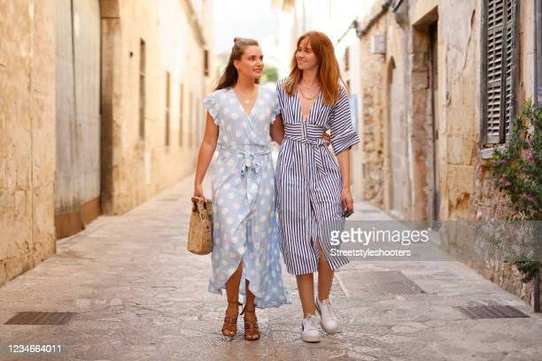 Influencer Marie von den Benken wearing a pastel blue wrap maxi dress with white all over polka dots, tied waist, v-neck and short ruffle sleeves by...