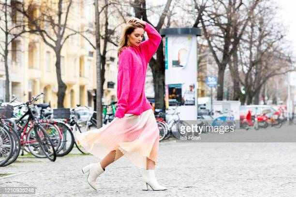 Influencer Marie von den Benken, wearing a pink pullover by Balenciaga and a apricot-rose color gradiented skirt by Jacquemus during a street style...