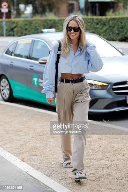 Influencer Mathilde Gohler, wearing a short blue blouse, beige pants, blue sandals by Chanel, a black belt and a black bag during Copenhagen Fashion...