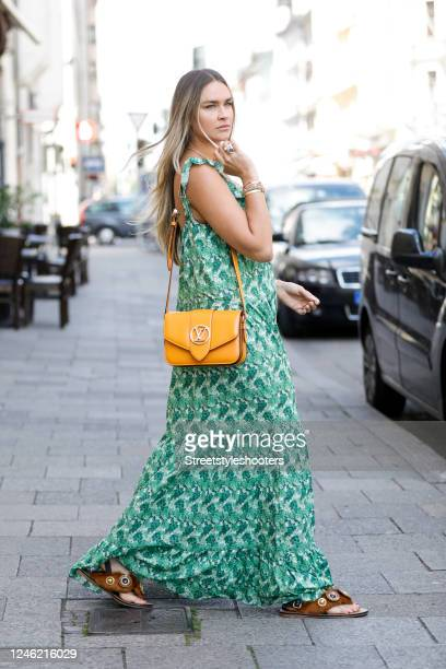 Influencer Nina Suess wearing a green pattered summer dress by Andrea Degreas, an orange colored bag by Louis Vuitton and brown fur thong sandals...