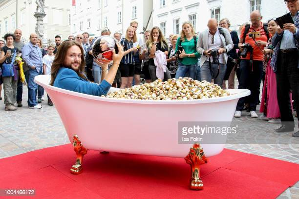 Influencer Riccardo Simonetti takes a bath in 'MozartKugeln' during he visits ReberFlagshipstore in Salzburg on July 23 2018 in Salzburg Austria