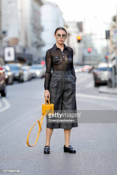 Influencer Sarah Lou Falk, wearing a black transparent blouse by Rina Scimento, dark grey patterned pants by Sandro, black loafers by Jonak, a dark...