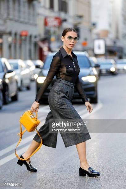 Influencer Sarah Lou Falk wearing a black transparent blouse by Rina Scimento dark grey patterned pants by Sandro black loafers by Jonak a dark...