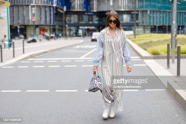 Influencer Sarah Lou Falk wearing a cream colored maxi dress with black pin stripes and light blue long sleeves with gathered detail by Munthe, brown...