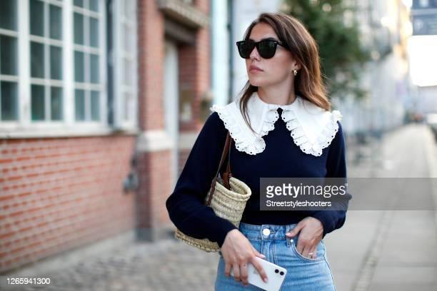 Influencer Sarah Lou Falk wearing a dark blue pollover with a big white collar by Sando Paris Jenas pants by Sando Paris a beige basket bag by Loewe...