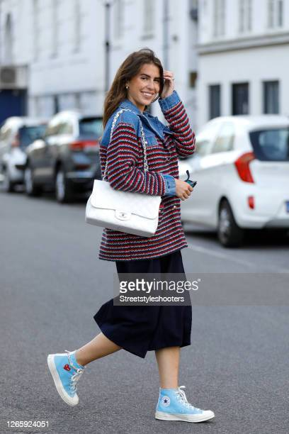 Influencer Sarah Lou Falk, wearing a jacket with red-black-blue stripes and a jeans collar by Sandro, black 3/4 pants by Pinko, light blue sneakers...