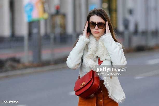 Influencer Sarah Lou Falk wearing a long cognac colored maxi skirt with gold buttons and high slits by Bally, a red bag by Bally, sunglasses by Gucci...