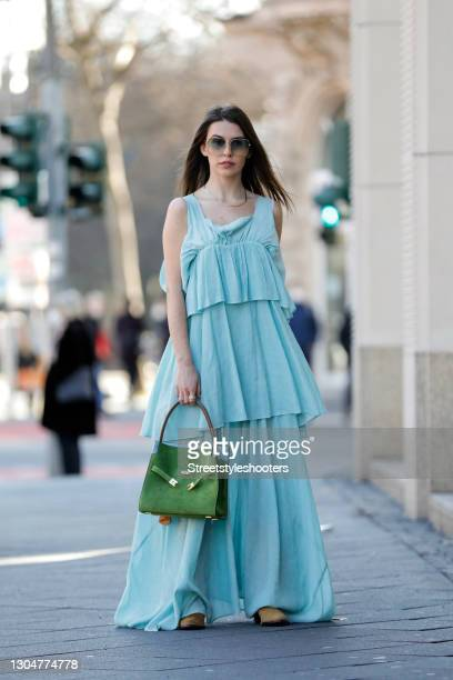 Influencer Sarah Lou Falk wearing a long light blue maxi dress by Rabens Saloner, brown boots by Sezane, sunglasses by Gucci and a green bag with...