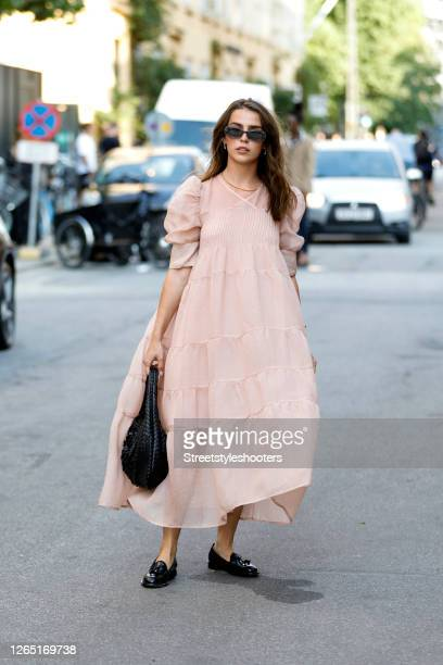 Influencer Sarah Lou Falk wearing a rose colored dress by Brigitte Herskind a black Vintage bag by Bottega Veneta black loafers by Scarosso and...