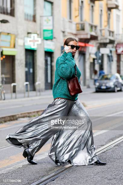 Influencer Sarah Lou Falk, wearing a silver colored jumpsuit by Rabens Saloner, a green Pullover by Sportmax, a brown bag by Sportmax, black boots by...