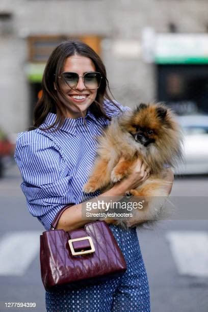 Influencer Sarah Lou Falk wearing a white blue striped blouse by Munthe blue patterned pants by Munthe a purple colored bag by Bally and sunglasses...