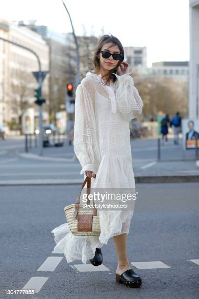 Influencer Sarah Lou Falk wearing black clog shoes by Bally, a long white maxi dress with lace details and polka dots by Tory Burch, a brown and...