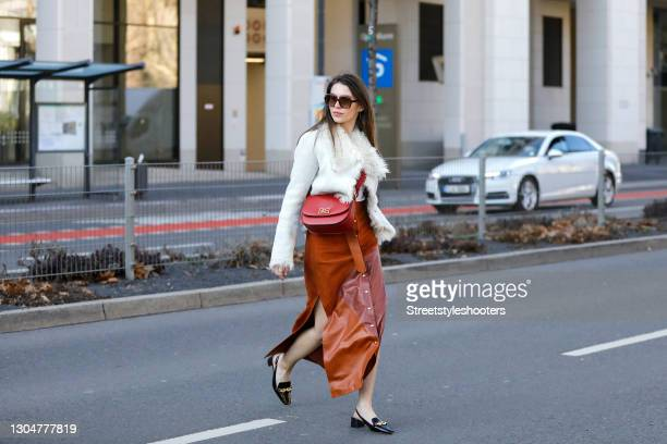 Influencer Sarah Lou Falk wearing black shoes by Tory Burch, a long cognac colored maxi skirt with gold buttons and high slits by Bally, a red bag by...