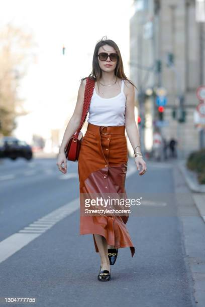 Influencer Sarah Lou Falk wearing black shoes by Tory Burch, a white top by Zara, a long cognac colored maxi skirt with gold buttons and high slits...