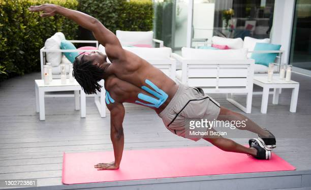 Influencer Shaka Smith practices yoga wearing SpiderTech pre-cut athletic tape at Giveback Day at The Artists Project on February 17, 2021 in Los...