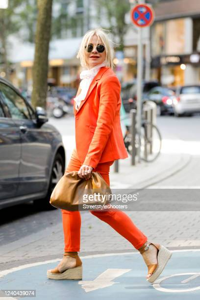 Influencer Simone Adams, wearing a orange balzer and orange pants by Elias Rumelis, a white blouse by Van Laack, cognac colored plateau sandals by...