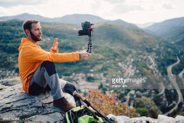 influencer tourist hiking and vlogging on the mountain top - vlogging stock photos and pictures