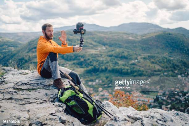 influencer tourist hiking and vlogging on the mountain top - influencer stock photos and pictures