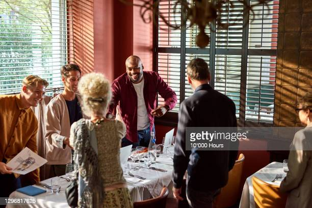 informal business meeting in restaurant with clients arriving - arrival stock pictures, royalty-free photos & images