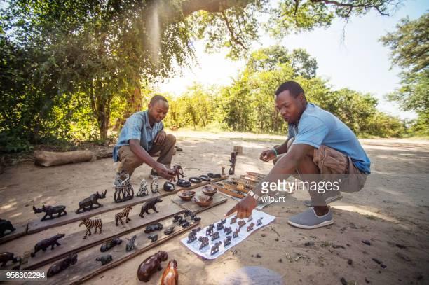 informal curios uomo d'affari che punta sotto un albero - mercato luogo per il commercio foto e immagini stock