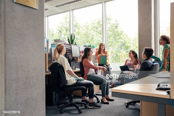 informal desk meeting - medium group of people stock pictures, royalty-free photos & images
