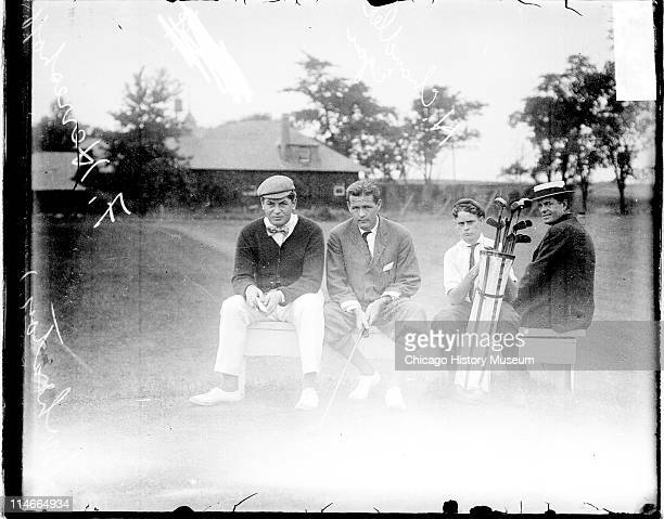 Informal fulllength group portrait of golfers Fred Herreshoff and H Chandler Egan sitting with a caddy and an unidentified man on a bench on the...